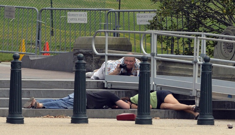 "People take cover as gun shots were being heard at the US Capitol in Washington, DC, on October 3, 2013. The US Capitol was placed on security lockdown Thursday after shots were fired outside the complex, senators said. ""Shots fired outside the Capitol. We are in temporary lock down,"" Senator Claire McCaskill said on Twitter. Police were seen running within the Capitol building and outside as vehicles swarmed to the scene. (Jewel Samad/Getty Images)"