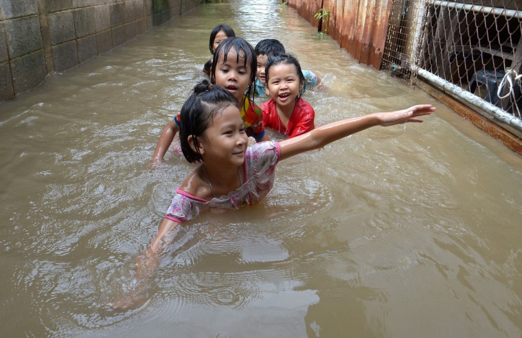 Thai children enjoy play in floodwaters at a buddhist temple in Pathum thani province, north of Bangkok. The Disaster Prevention and Mitigation Department reported that 27 provinces in Thailand are still flooded and 31 people have died due to the flood. (Pornchai Kittiwongsakul/Getty Images)