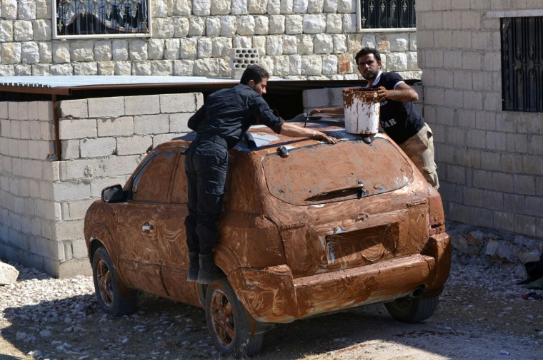 Rebel fighters cover a car in mud for camouflage at an undisclosed location in Syria's northwestern province of Idlib. The world's chemical watchdog said it will send a second team of inspectors to help dismantle Syria's arsenal, as regime warplanes bombed rebels in the northwest of the country. (Mohamad Jadaan/Getty Images)