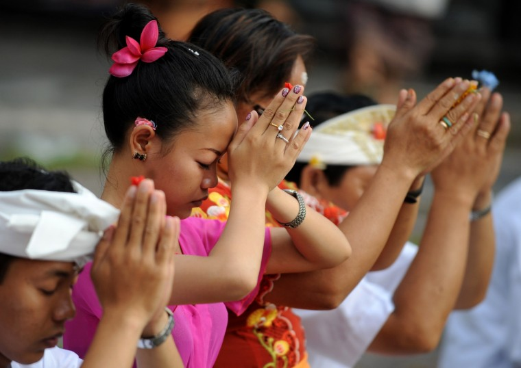 Balinese people pray as they celebrate the religious festival of Galungan at a temple in Denpasar, on Indonesia's tourist island of Bali. Devotees celebrate Galungan Day, or the earth's celebration, to thank God for the creation of the earth and its content. (Sonny Tumbelaka/Getty Images)