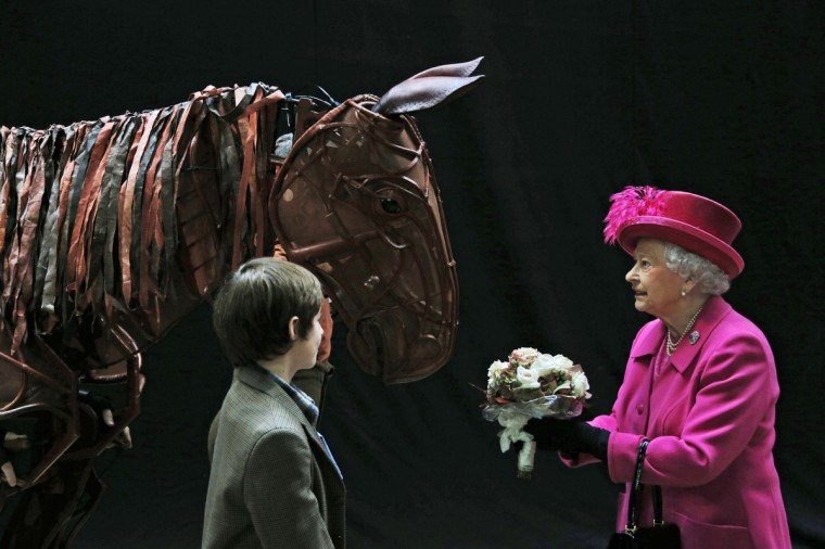 Britain's Queen Elizabeth II receives flowers from a child actor as she inspects the horse prop from the theatre production 'War Horse' at the National Theatre in London during a visit to commemorate the institutions 50th anniversary. (Lefteris Pitarakis/Getty Images)Britain's Queen Elizabeth II receives flowers from a child actor as she inspects the horse prop from the theatre production 'War Horse' at the National Theatre in London during a visit to commemorate the institutions 50th anniversary. (Lefteris Pitarakis/Getty Images)