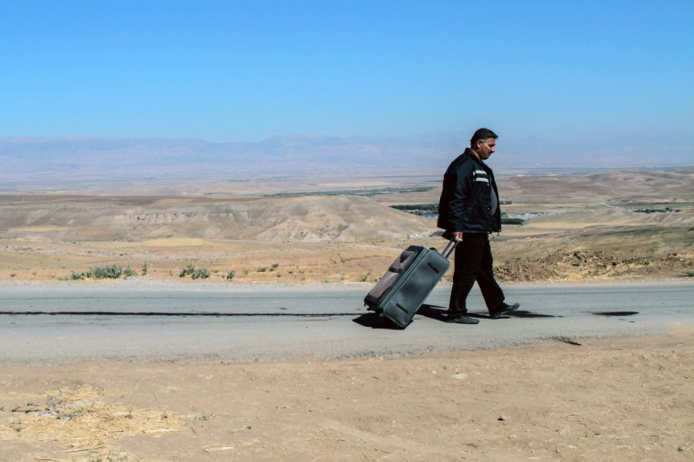 A Syrian refugee rolls his suitcase after he and others are refused entry from northeastern Syria into northern Iraq by the Kurdistan Region Government (KRG) based in northern Iraq. The group of more than 150 Syrians looking for refuge in neighboring Iraq Kurdistan waited an hour but were refused entry and had to return to Syria. This crossing has been closed since the end of May, allowing only humanitarian aid and those who are ill through. (Mauricio Morales/Getty Images)