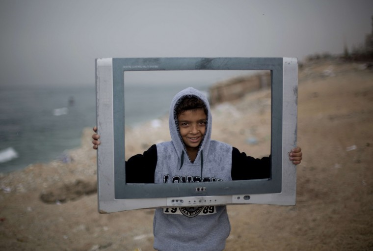 A Palestinian boy poses inside the frame of a broken television outside his house in al-Shatee refugee camp in Gaza City. (Mohammed Abed/Getty Images)