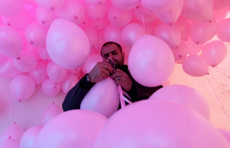 "A man prepares a bunch of balloons the Yemeni capital Sanaa on the occasion of the annual campaign ""Breast Cancer Awareness Month"" to increase awareness and promote treatment of breast cancer. (Mohammed Huwais/Getty Images)"