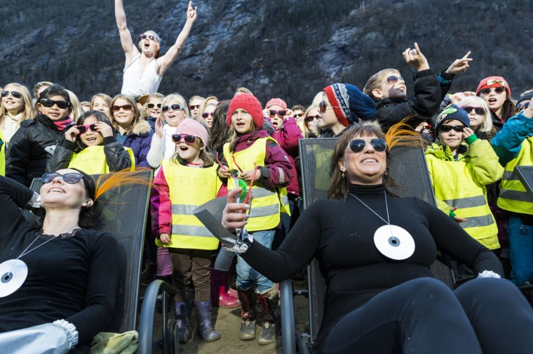 "People cheer during an inauguration of the huge sun mirrors (""Solspeilet"") set up on the hillside above Rjukan, to reflect sunlight down on the town square,100 years after the idea was first released. Sun-starved residents of a remote Norwegian village unveiled an ingenious mirror system Wednesday to bring natural light to their mountain valley home, enveloped in darkness for half of the year. (Krister Soerboe/Getty Images)"