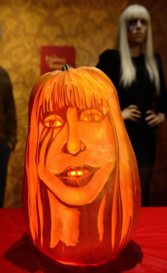 Pumpkin carver Hugh McCahon carves a pumpkin in the likeness of US singer Lady Gaga in front of her wax figure at Madame Tussauds in New York on October 22, 2013. (Emmanuel Dunand/Getty Images)