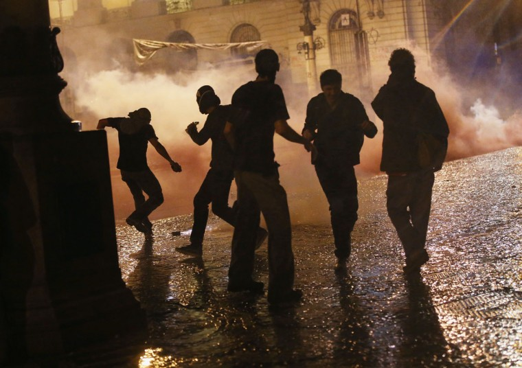 Protesters react as tear gas is fired by the police to disperse protesters calling for better public education and services on October 7, 2013 in Rio de Janeiro, Brazil. While the majority of protesters were peaceful, a small group fired incendiary devices and the police eventually dispersed the crowd with tear gas. The last few weeks have seen a citywide strike by union education workers in Rio and police used tear gas to disperse a group of around 100 protesting teachers last week. (Mario Tama/Getty Images)