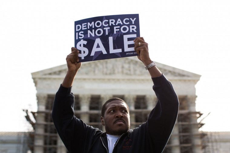 Cornell Woolridge holds a sign as he rallies against money in politics at the Supreme Court in Washington, on October 8, 2013. On Tuesday, the Supreme Court heard oral arguments in McCutcheon v. Federal Election Committee, a first amendment case about how much money an individual can contribute directly to political campaigns. (Drew Angerer/Getty Images)