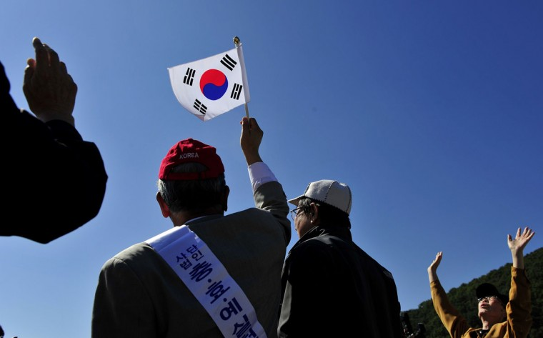 North Korean defectors react after releasing helium balloons carrying leaflets during an anti-North Korea rally denouncing North Korea's decision to postpone a reunion for families separated by the Korean War near the border in Paju, north of Seoul. They flew the 200,000 propaganda leaflets across the border. (Truth LEEM / AFP/Getty Images)