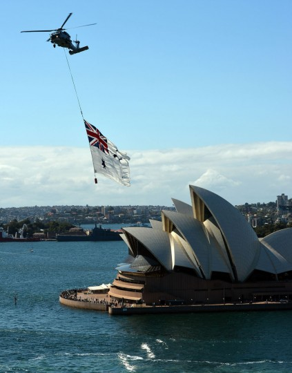 A Royal Australian Navy Seahawk helicopter flies the Australian Navy White over the Sydney Opera House on Oct. 4, 2013 as part of celebrations to commemorate 100 years since the Royal Australian Navy's fleet first entered the city's waters. Ships from nations including China, Thailand, the United States, Malaysia, France, Japan and former colonial power Britain passed through the heads into the famous harbor where they joined 16 tall ships from around the world in preparation for a ceremonial fleet review. (SAEED KHAN / AFP/Getty Images)