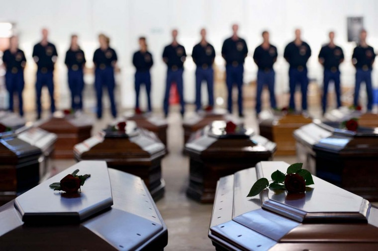 People stand next to Coffins of victims in a hangar of the Lampedusa airport on October 5, 2013 after a boat with migrants sank, killing more than hundred people. Italy mourned today the 300 African asylum-seekers feared dead in the worst ever Mediterranean refugee disaster, as the government appealed for Europe to stem the influx of migrants. Italian emergency services hoped to resume the search for bodies despite rough seas after the accident, in which 111 African asylum-seekers are confirmed dead and around 200 more are still missing. (Alberto Pizzoli/AFP)