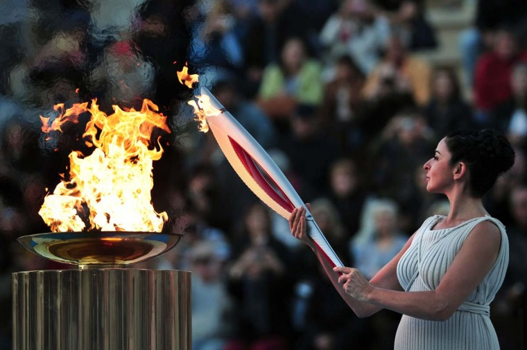 Actress Ino Menegaki, playing a high priestess lights a torch from a cauldron on October 5, 2013,during the handover ceremony of the Olympic Flame for the XXII Winter Olympic Games Sochi 2014 at the Panathenaic stadium in Athens. (Louis Gouliamaki/AFP)