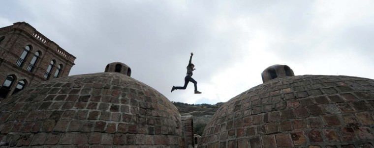 A boy jumps over the roofs of ancient Sulphur Bathhouses in the Georgian capital Tbilisi on October 5, 2013. (Vano Shlamov/AFP)