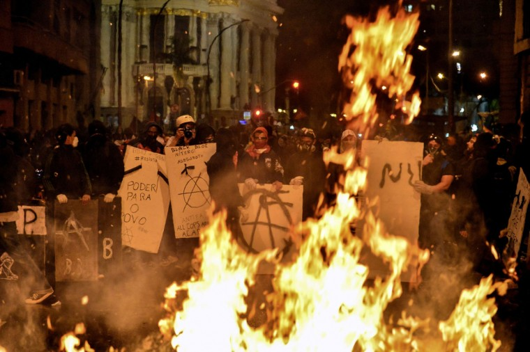 Masked demonstrators burn trash outside the City Hall in Rio de Janeiro, following a peaceful teachers' protest demanding better working conditions and against police beating, on October 7, 2013. (Yasuyoshi Chiba/AFP/Getty Images)
