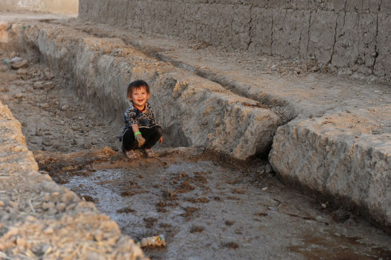 """An Afghan child looks on as she plays in a canal on the outskirts of Mazar-i-Sharif on October 8, 2013. Some nine million Afghans or 36 percent of the population are living in """"absolute poverty"""" while another 37 percent live barely above the poverty line, according to a UN report. (Farshad Usyan/AFP/Getty Images)"""