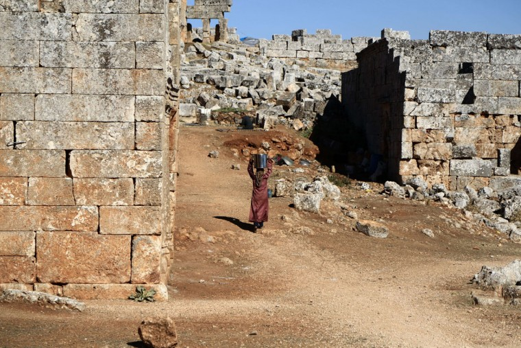 "A Syrian refugee woman carries water on her head that she collected from a nearby village as she returns to where she is residing in the ancient Byzantine-Christian city of Serjilla, in the Jabal al-Zawiya region of Syria on October 8, 2013. The woman pictured she fled her home due to the ongoing conflict between government and opposition forces. Serjilla, which has been deserted for over 1500 years, is situated in an elevated area of limestone known as Belus Massif and is known as being one of Syria's ""Dead Cities"" or ""Forgotten Cities"", a group of 700 abandoned settlement in the northwest area between Aleppo and Hama, which date back to fifth century. (Mezar Matar/AFP/Getty Images)"
