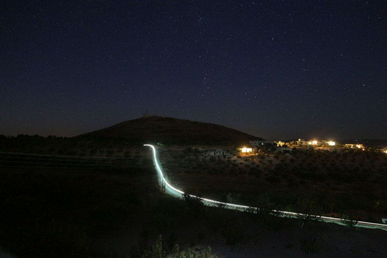 A picture taken with a long exposure shows the light of a motorcycle as it drives along a road in the Jabal al-Zawiya region of Syria's northwestern province of Idlib on Tuesday. (MEZAR MATAR/AFP/Getty Images)