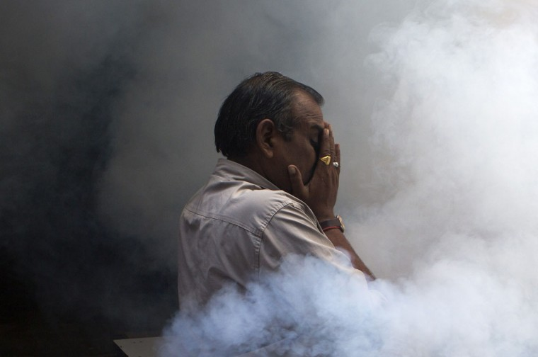 An Indian pedestrian protects his face while engulfed in a cloud of pesticide during a dengue prevention spraying in the Old Quarters in New Delhi. (Andrew Caballero-Reynolds / AFP/Getty Images)