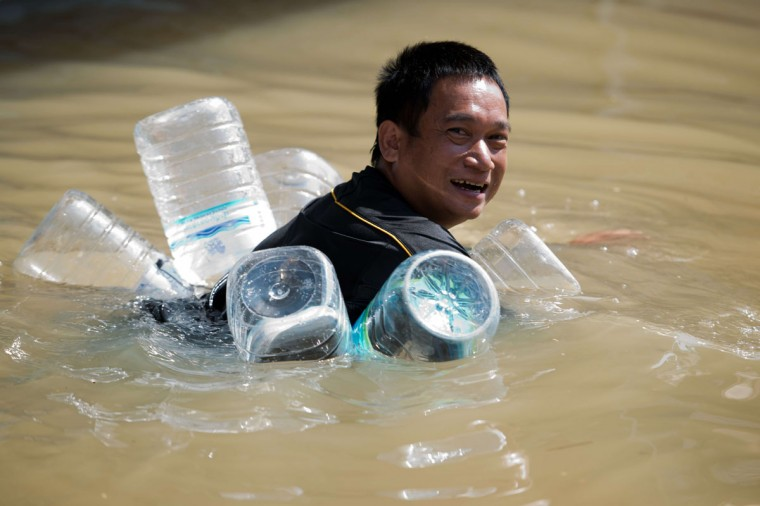 A man swims in floodwaters with a self-made floating device made of plastic bottles Thursday in Kabin Buri, east of Bangkok.. The Disaster Prevention and Mitigation Department reported that 27 provinces in Thailand are still flooded and 31 people have died due to floods that have drenched swathes of Southeast Asia in recent weeks. (NICOLAS ASFOURI/AFP/Getty Images)