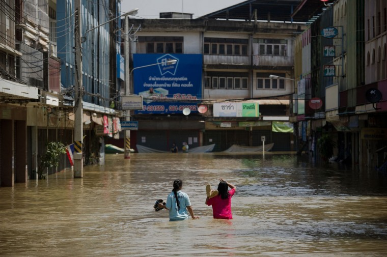 Two young women walk through floodwaters in Kabin Buri, east of Bangkok. The Disaster Prevention and Mitigation Department reported that 27 provinces in Thailand are still flooded and 31 people have died due to floods that have drenched swathes of Southeast Asia in recent weeks. (NICOLAS ASFOURI / AFP/Getty Images)