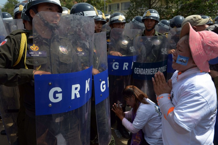 Cambodian land protesters gesture with military police officials during the 28th World Habitat day in Phnom Penh. Cambodian land protesters and land rights activists celebrate the 28th World Habitat day. (TANG CHHIN SOTHY / AFP/Getty Images)