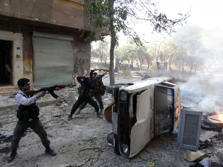 Opposition fighters open fire, taking cover from behind a car during fighting in the Salaheddin district of the northern Syrian city of Aleppo. (KARAM AL-MASRI / AFP/Getty Images)