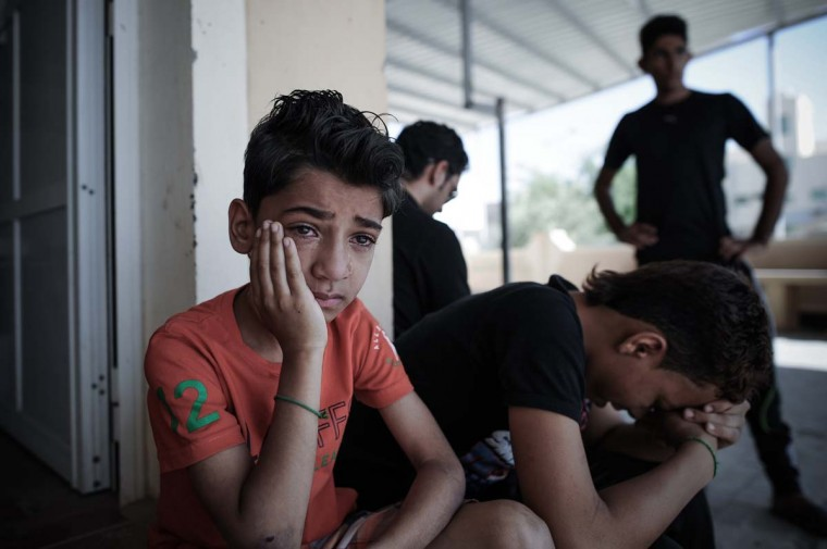 A Bahraini boy mourns during the funeral of Yussef al-Nashmi, who died in hospital the day before as he was detained by Bahraini authorities since on August 17, in the western Manama suburb of Jidd Hafs, on October 12, 2013. Anti-riot police in Bahrain used buckshot, sound grenades and tear gas to disperse hundreds of Shiite protesters trying to reach Pearl Square in Manama after the funeral of Nashmi. (Mohammed Al Shaikh/AFP)