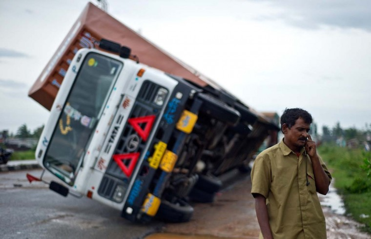 Indian truck driver Jairam Yadav speaks on his mobile phone after his truck carrying Toyota cars was overturned by strong wind on the National Highway linking Andhra Pradesh and Odisha on October 13, 2013. Cyclone Phailin left a trail of destruction along India's east coast and up to seven people dead after the biggest evacuation in the country's history helped minimise casualties. (Manan Vatsyayana/AFP)