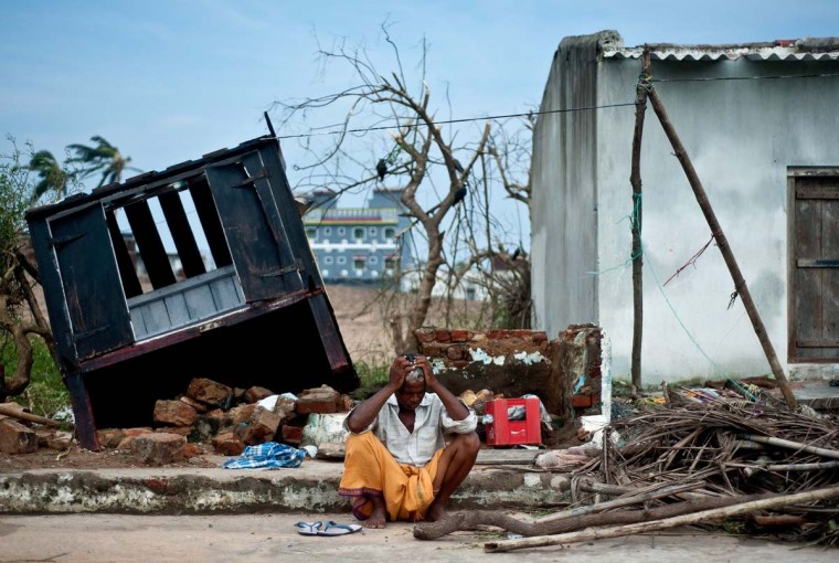 Bhagwan, a coconut-seller, reacts as he sits in front of his destroyed shop in Gopalpur on October 13, 2013. Cyclone Phailin left a trail of destruction along India's east coast and up to seven people dead after the biggest evacuation in the country's history helped minimise casualties. (Manan Vatsyayana/AFP)