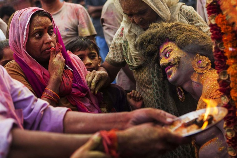 An Indian Hindu devotee looks AT an idol as others perform rituals as part of the Durga Puja festival in New Delhi on October 13, 2013. Durga Puja commemorates the slaying of demon king Mahishasur by goddess Durga, marking the triumph of good over evil. (Andrew Caballero-Reynolds/AFP)
