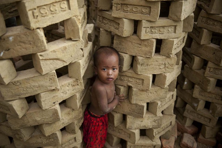 This picture taken on October 13, 2013 shows a child standing next to drying bricks at a factory on the outskirts of Yangon. Demand for property in Yangon has surged as Myanmar undergoes rapid change since shedding the isolation of junta rule. Sales prices have doubled or even trebled over the past two years in some neighbourhoods and developers are scrambling to build new properties. But despite the fact that sales prices are several times higher than Bangkok in neighbouring Thailand, Yangon still struggles with poor transport links, few modern condominiums and irregular electricity and Internet access. (Ye Aung Thuy/AFP)