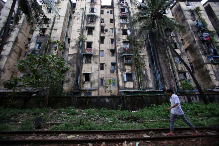 This picture taken on October 10, 2013 shows a man walking along railway tracks past old apartment blocks in Yangon. Demand for property in Yangon has surged as Myanmar undergoes rapid change since shedding the isolation of junta rule. Sales prices have doubled or even trebled over the past two years in some neighbourhoods and developers are scrambling to build new properties. But despite the fact that sales prices are several times higher than Bangkok in neighbouring Thailand, Yangon still struggles with poor transport links, few modern condominiums and irregular electricity and Internet access. (Ye Aung Thuy/AFP)