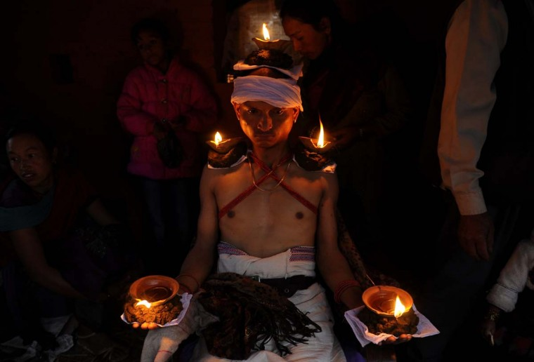 A Nepalese Hindu devotee holds burning oil lamps on his head and palms for six hours on the tenth day of Hindu's biggest festival, Dashain (Durga Puja), in Bhaktapur on the outskirts of Kathmandu on October 14, 2013. Dashain is the longest and the most auspicious festival in the Nepalese calendar and celebrates the triumph of good over evil. (Prakash Mathema/AFP)