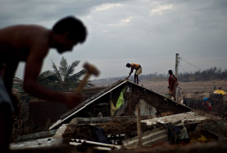 Indian fishermen fix their houses damaged during cyclon Phailin at Nalianuagaon in Ganjam district of Odisha. While the biggest evacuation in Indian history was hailed for minimizing loss of life, already poor fishermen and farmers have returned to their villages this week to discover the few possessions they had have been destroyed. (MANAN VATSYAYANA / AFP/Getty Images)