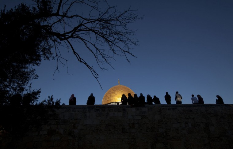"""Palestinian Muslim worshippers sit on a wall in front of the golden dome inside the Al-Aqsa Mosque compound, Islam's third holiest shrine, in Jerusalem's old city following morning prayers on the Muslim holiday of Eid al-Adha or """"The Feast of Sacrifice."""" (AHMAD GHARABLI / AFP/Getty Images)"""