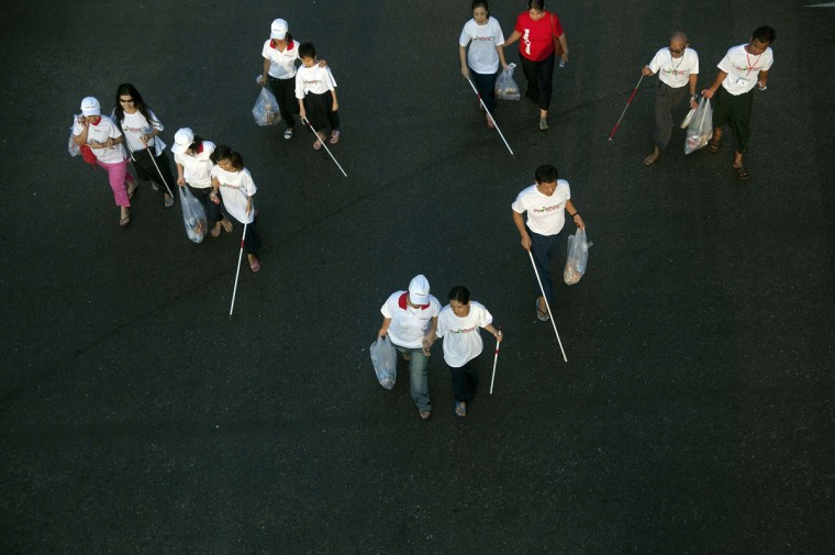 Blind and visually impaired people are assisted as they participate in a walk to mark White Cane Day in Yangon. (Aung Thu / AFP/Getty Images)