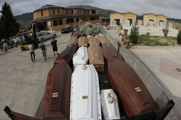 A truck transporting coffins arrives at the Piano Gatta's cemetery before the funeral of immigrants in Agrigento in Sicily. Dozens of burials in anonymous vaults began yesterday in a small cemetery of Piano Gatta, even though Prime Minister Enrico Letta had promised to hold a state funeral for the victims. (MARCELLO PATERNOSTRO / AFP/Getty Images)