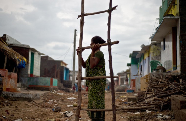 An Indian woman carries a wooden ladder to fix her house damaged during cyclon Phailin at Nalianuagaon in Ganjam district of Odisha. (MANAN VATSYAYANA / AFP/Getty Images)