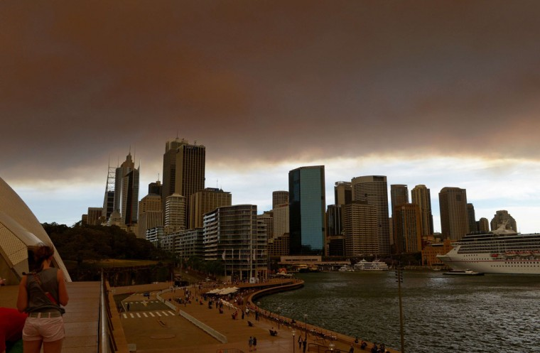 Smoke and ash from wildfires burning across the state of New South Wales blankets the Sydney city skyline on October 17, 2013. Seven major blazes were burning across the state, fanned by high, erratic winds in unseasonably warm 34 Celsius (93 Fahrenheit) weather, with infernos at Springwood and Lithgow in the Blue Mountains west of Sydney sending thick plumes of smoke and ash across the city. (Greg Wood/AFP/Getty Images)