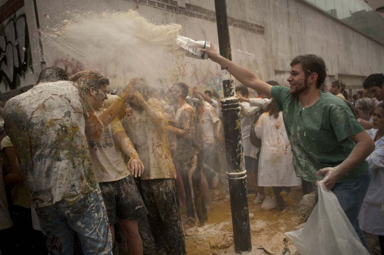 A medical student throws flour on freshers of the Faculty of Medicine during a hazing at the University of Granada, in Granada on October 17, 2013. (Jorge Guerrero/AFP)