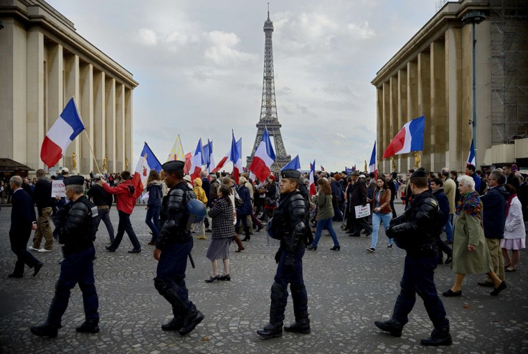 Members of the French riot police walk past the Eiffel tower and supporters of the fundamentalist christian group Civitas Institute as they take part in a demonstration on October 20, 2013 in Paris. (ERIC FEFERBERG / AFP/Getty Images)