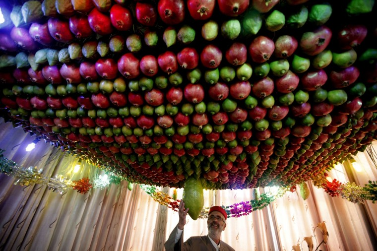A Samaritan man stands under a Sukkah made of fruits inside his house during the holiday of Sukkot (the Tabernacles Feast) celebrations on Mount Gerizim near the northern West Bank city of Nablus. (JAAFAR ASHTIYEH / AFP/Getty Images)