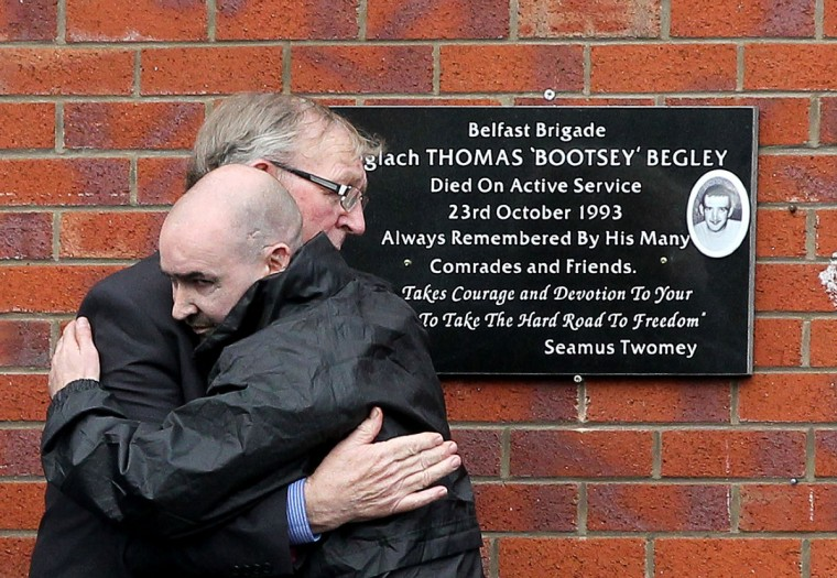 Sean Kelly, right, hugs Billy Begley, father of Thomas Begley, during a commemoration service for the Shankill road bomber Thomas Begley in Belfast, Northern Ireland, on October 20, 2013. Thomas Begley died in 1993 when the bomb he was planting on the Shankill Road in Belfast exploded prematurely, killing nine people and injuring more than 50. (PETER MUHLY / AFP/Getty Images)
