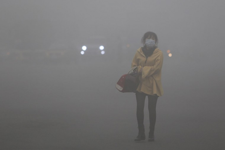 A woman wearing a face mask walks in heavy smog in Harbin, located in northeast China's Heilongjiang province. (AFP/Getty photo)