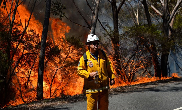 """A firefighter monitors a back burn near Mount Victoria in the Blue Mountains on October 21, 2013, as volunteer fire brigades race to tame an enormous blaze, with officials warning it could merge with others to create a """"mega-fire"""" if weather conditions worsen. Crews have been battling fires that flared in high winds and searing heat across the state of New South Wales last week with more than 200 homes so far destroyed and many others damaged. (William West/AFP/Getty Images)"""