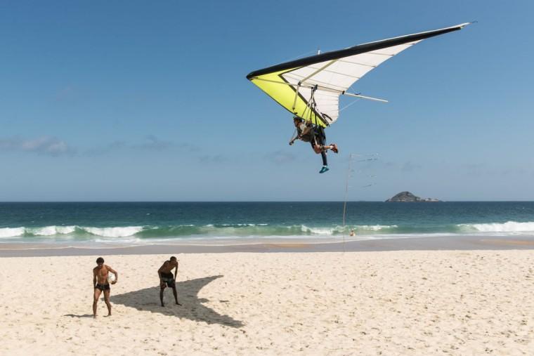 A hang glider lands on Sao Conrad beach in Rio de Janeiro, Brazil. (YASUYOSHI CHIBA / AFP/Getty Images)