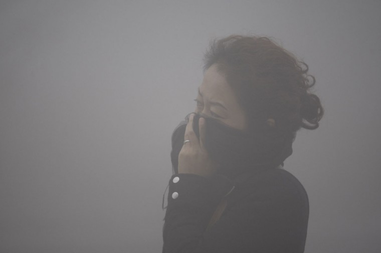 A woman covers her mouth with her scarf in the smog in Harbin. (AFP/Getty Images)