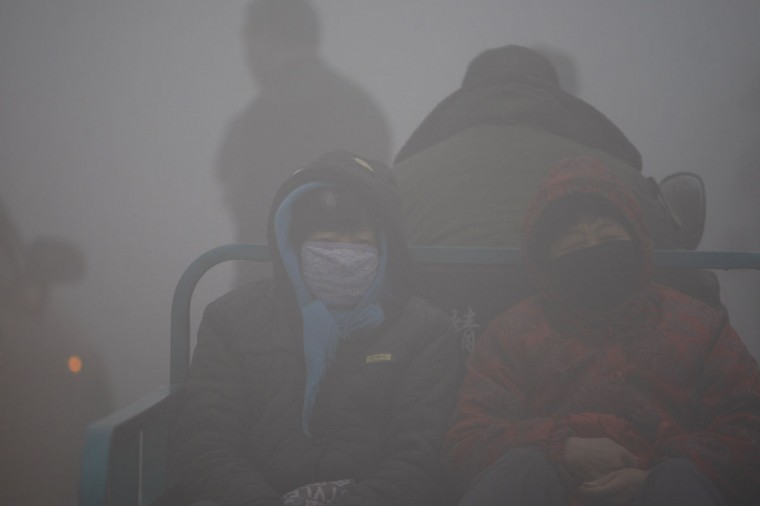Local residents travel on a tricycle in the smog in Harbin. (AFP/Getty Images)