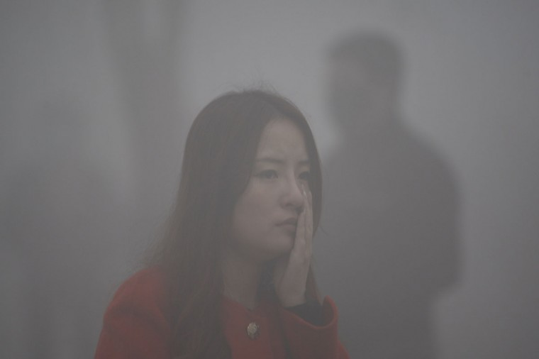 A woman walks in the smog in Harbin. (AFP/Getty Images)