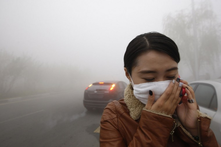 A woman wearing a mask covers her mouth with her hands as she walks in the smog in Harbin. (AFP/Getty Images)